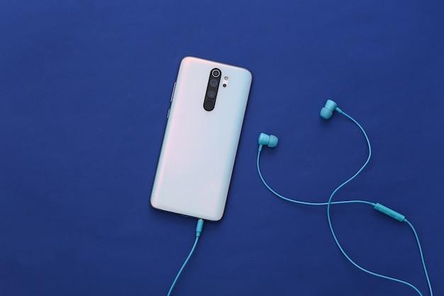 Smartfon i słuchawki w klasycznym niebieskim kolorze.