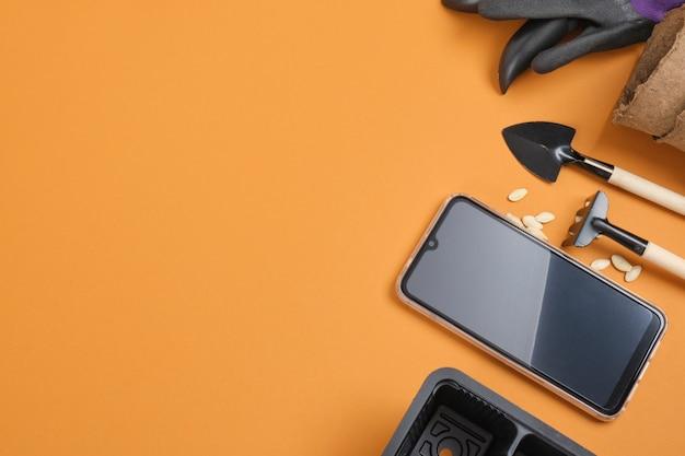 Smartfon i sprzęt ogrodowy na brązowym tle, koncepcja bloga ogrodnika