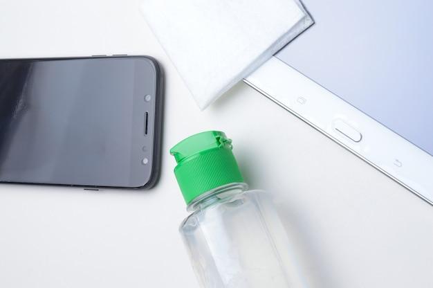 Smartfon i tablet na białym tle w miejscu z butelką żelu dezynfekującego i serwetką. leczenie antywirusowe i antybakteryjne gadżetów do noszenia. .