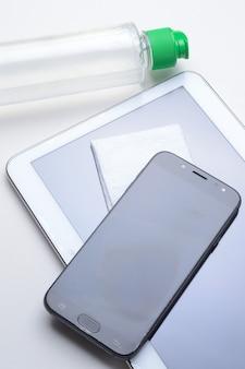 Smartfon i tablet na białym tle w miejscu z butelką żelu dezynfekującego i serwetką. leczenie przeciwwirusowe i antybakteryjne gadżetów do noszenia.