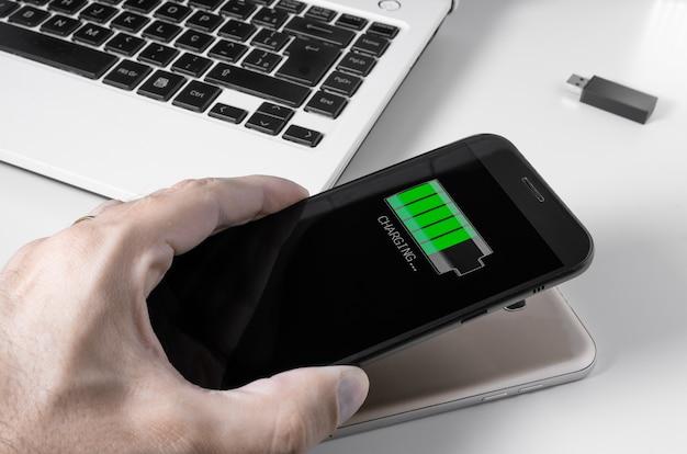 Smartfon jest ładowany przez inne urządzenie poprzez ładowanie bezprzewodowe