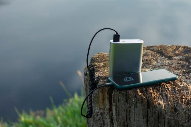 Smartfon jest ładowany za pomocą przenośnej ładowarki. power bank ładuje telefon na świeżym powietrzu z plecakiem do turystyki na tle przyrody i rzeki.