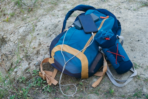 Smartfon jest ładowany za pomocą przenośnej ładowarki. power bank ładuje telefon na zewnątrz z plecakiem do turystyki na łonie natury.