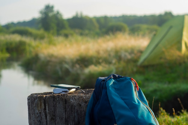 Smartfon jest ładowany za pomocą przenośnej ładowarki. power bank ładuje telefon na zewnątrz z plecakiem na tle namiotu.