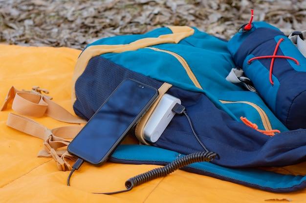 Smartfon jest ładowany za pomocą przenośnej ładowarki. power bank z telefonem komórkowym na śpiworze z plecakiem.