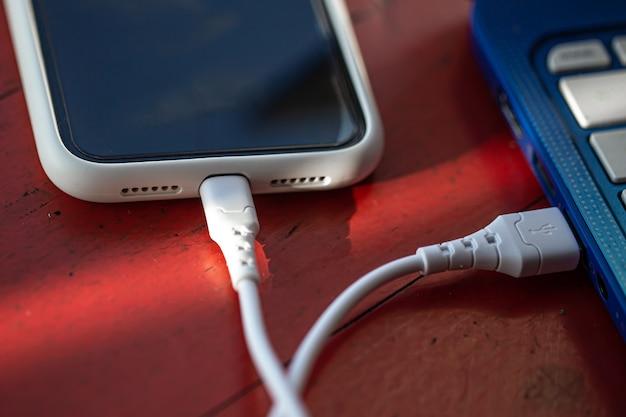 Smartfon jest podłączony do laptopa za pomocą kabla usb
