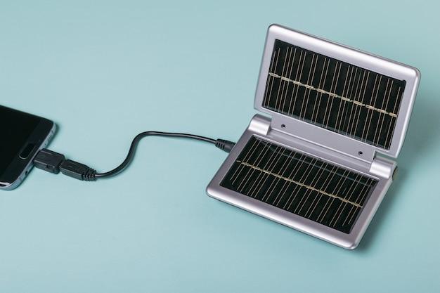 Smartfon jest podłączony do urządzenia zasilanego energią słoneczną w celu ładowania. wykorzystanie energii słonecznej. technologia przyszłości.