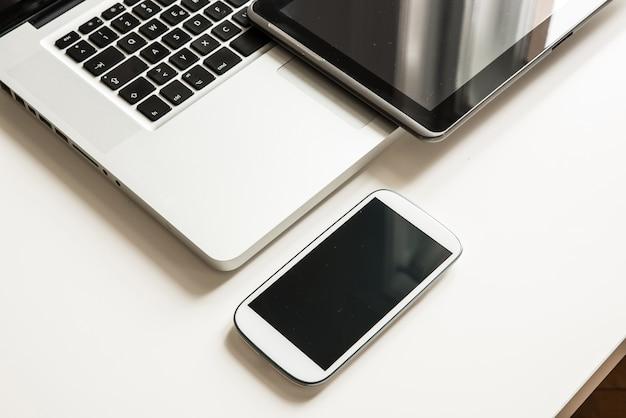 Smartfon, komputer przenośny i komputer typu tablet razem na pulpicie.
