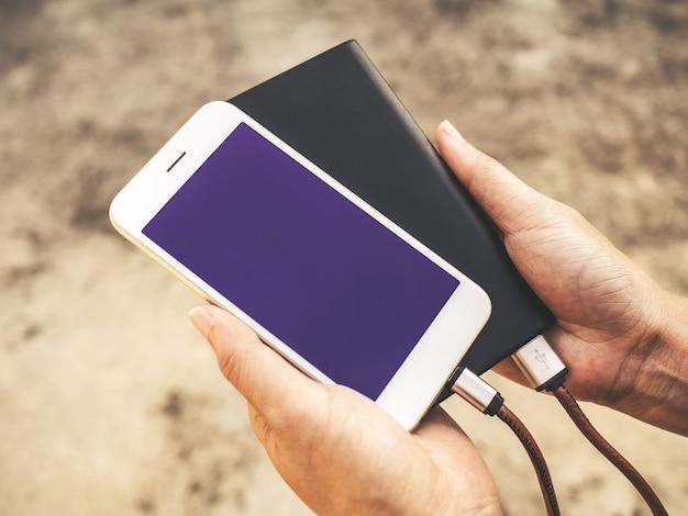 Smartfon ładuje baterię z zewnętrznego zasilacza