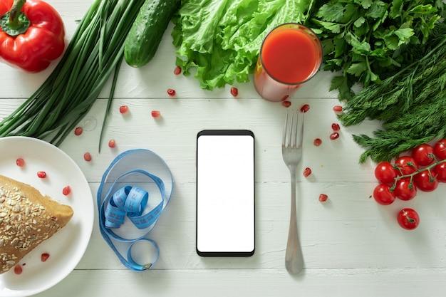 Smartfon leży na stole z dietetycznymi warzywami. miejsce na twój tekst.