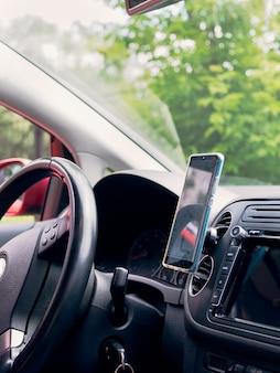 Smartfon montowany wewnątrz czerwonego samochodu obok kierownicy do nawigacji