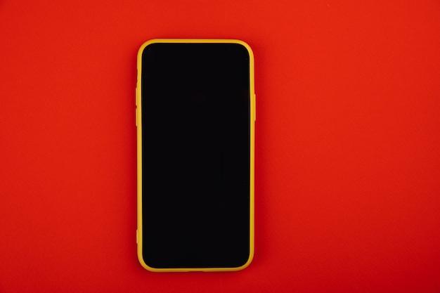 Smartfon na białym tle na czerwonym tle.