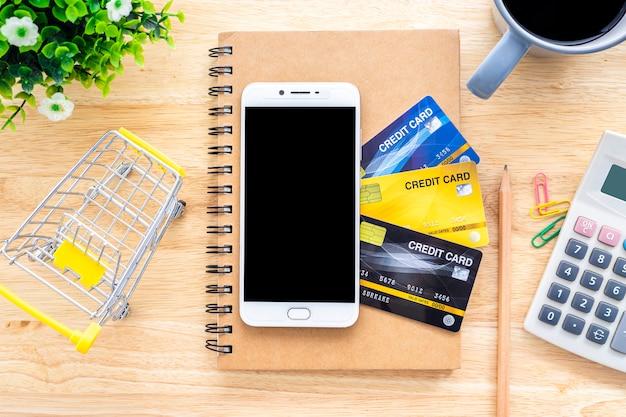 Smartfon na karty kredytowe, notatnik, doniczka, koszyk, kalkulator i filiżanka kawy na drewnianym tle, bankowość internetowa widok z góry stół biurowy