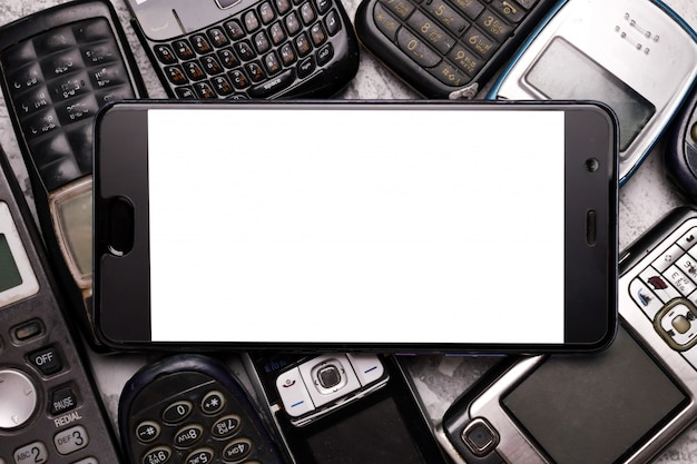 Smartfon na stosie przestarzałych telefonów komórkowych.
