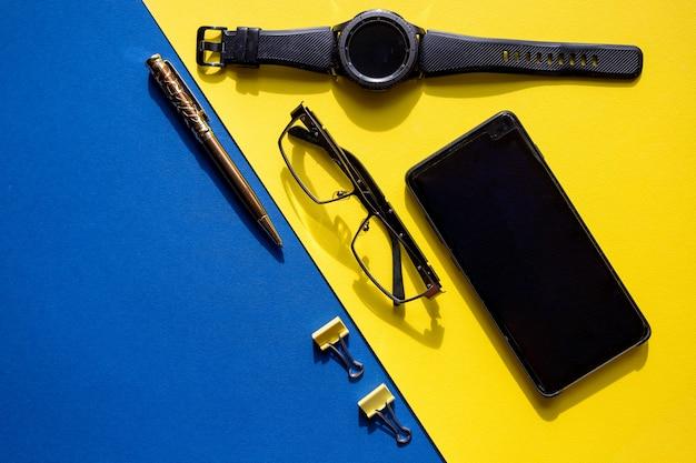 Smartfon, okulary, elegancki zegarek, długopis i klipsy