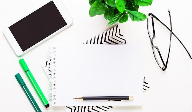 Smartfon, okulary, zielona roślina, zielone markery, pusty notatnik i długopis na pulpicie. leżał na płasko.