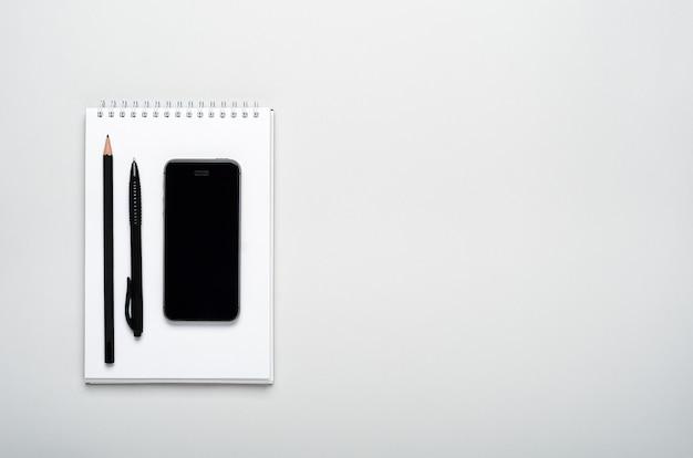 Smartfon, ołówek, długopis w notatniku