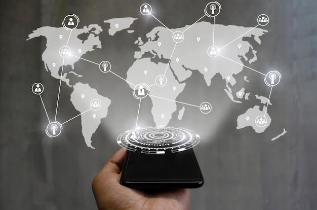 Smartfon pod ręką z globalnym łączem mediów łączącym się na tle międzynarodowej mapy świata