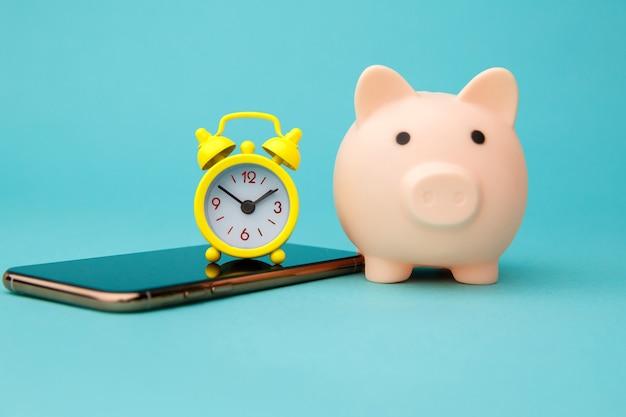 Smartfon, różowa skarbonka i budzik na niebiesko.
