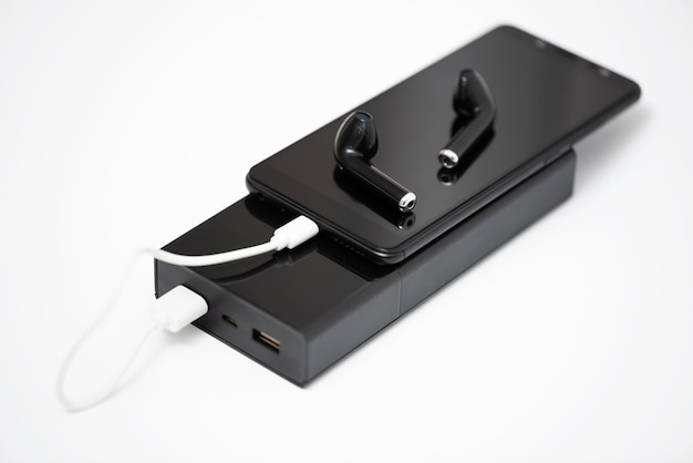 Smartfon, słuchawki bezprzewodowe i power bank na białym tle,