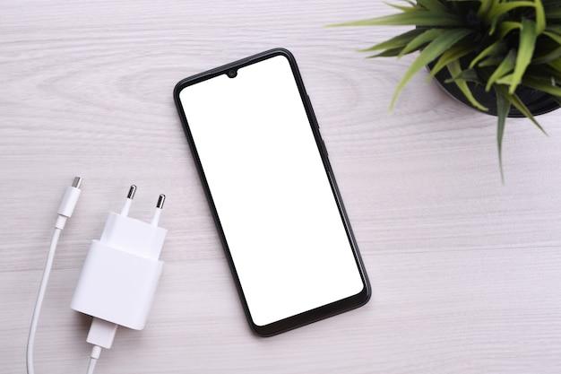 Smartfon telefonu komórkowego z białym ekranem dla tekstu, obraz na jasnym wadliwym stole z ładowaniem