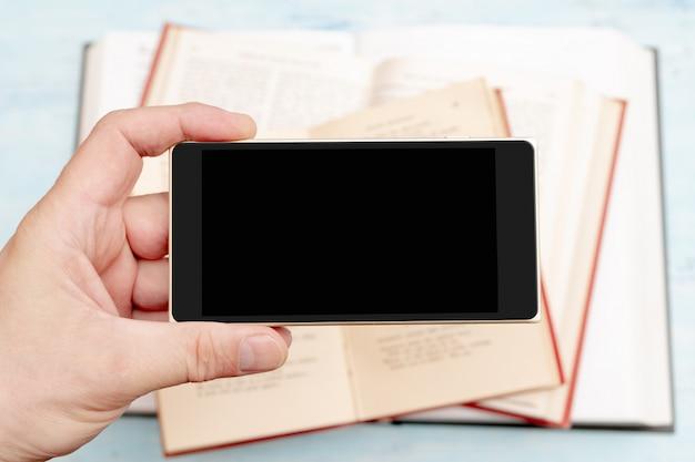 Smartfon w ręce mężczyzny. nowoczesny telefon gadżetowy. wyświetlacz telefonu. stare papierowe książki.