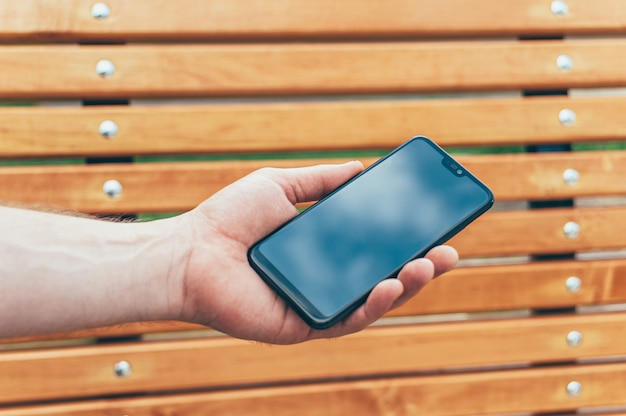 Smartfon w ręku człowieka, na tle drewnianej ławki.