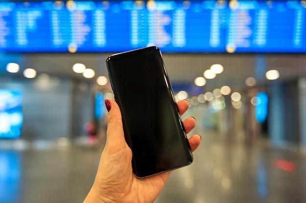 Smartfon w ręku na tle tablicy informacyjnej na lotnisku.