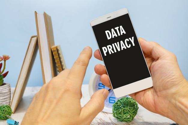 Smartfon w ręku z napisem prywatność danych obok materiałów biurowych