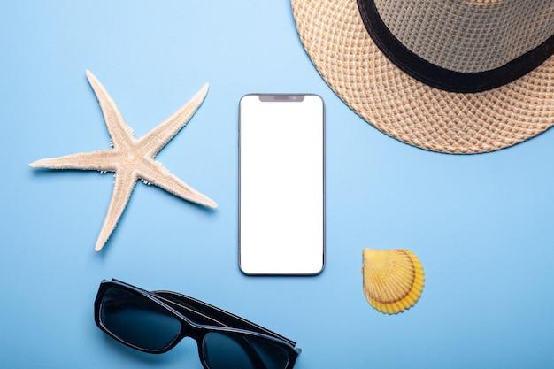 Smartfon z białym pustym ekranem w pobliżu kapelusza, rozgwiazdy i muszli na niebiesko