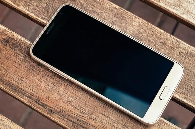 Smartfon z czarnym ekranem na drewnianym stole, widok z góry