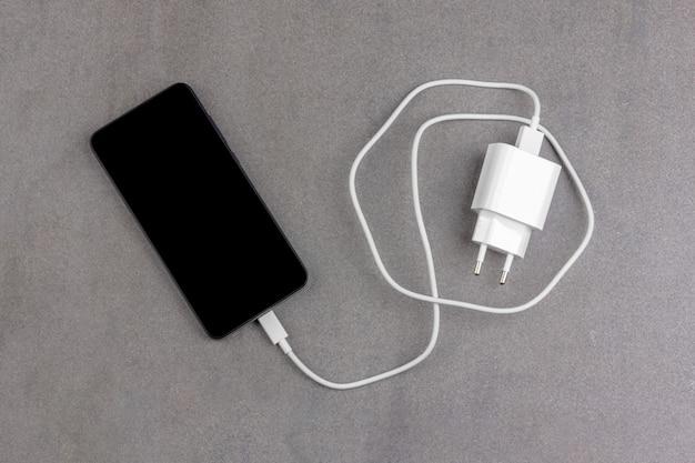 Smartfon z czarnym ekranem z białą ładowarką
