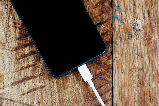 Smartfon z czarnym ekranem z przewodem od ładowarki