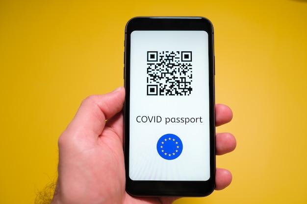 Smartfon z elektronicznym paszportem odpornościowym cyfrowym paszportem zdrowotnym covid pass z kodem qr w ręce mężczyzny
