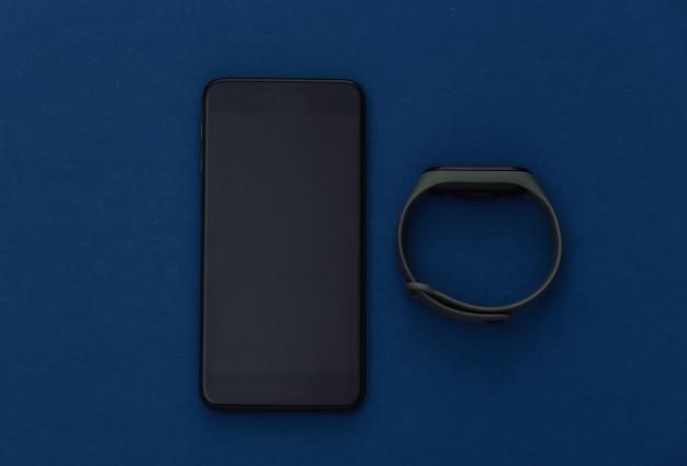 Smartfon z inteligentną bransoletką na klasycznym niebieskim tle. nowoczesne gadżety. kolor 2020. widok z góry.