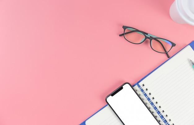 Smartfon z książką i okulary na różowym pastelowym tle