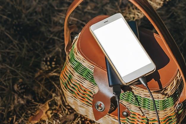 Smartfon z ładowaniem power bank na kosz w lesie. koncepcja na temat rekreacji na świeżym powietrzu.