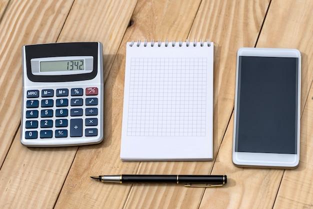 Smartfon z notatnikiem, długopisem i kalkulatorem na drewnianym stole