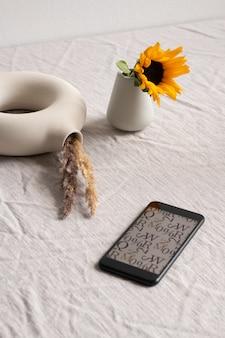 Smartfon z obrazem liter i symboli na ekranie, małym słonecznikiem w szkle ceramicznym i kreatywnym wazonem w kształcie pierścienia z suszonymi kolcami