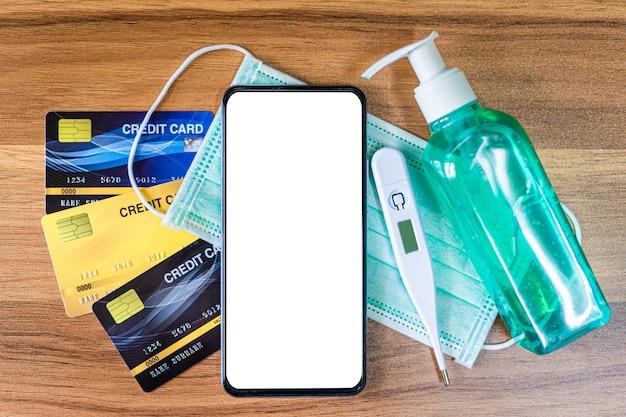 Smartfon z ochronną jednorazową maską medyczną, termometrem, kartami kredytowymi i alkoholowym środkiem odkażającym do rąk na podłoże drewniane