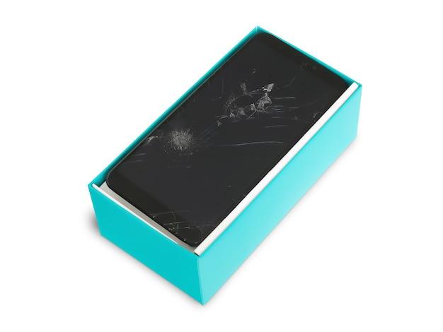Smartfon z pękniętym ekranem w niebieskim pudełku na białym tle, wadliwy smartfon, koncepcja produkcji urządzenia niskiej jakości