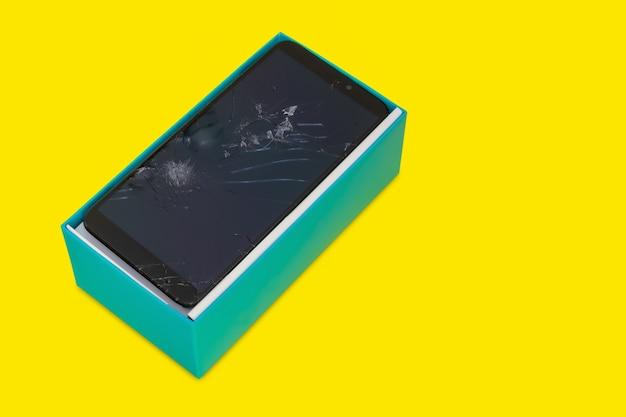 Smartfon z pękniętym ekranem w niebieskim pudełku na prezent na żółtym tle