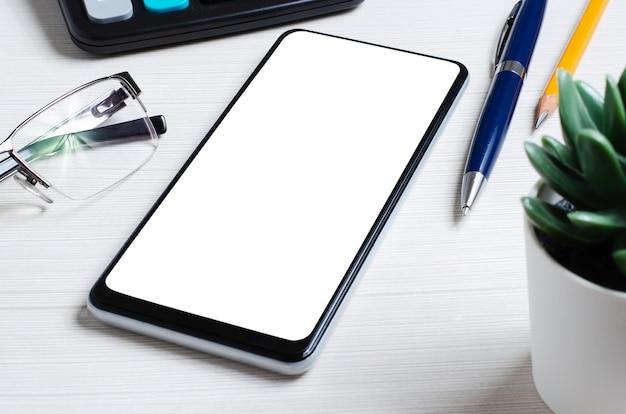 Smartfon z pustym ekranem na białym stole. skopiuj miejsce. pojęcie inwestowania online, handlu lub handlu akcjami.