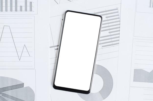 Smartfon z pustym ekranem na tle wykresów i wykresów. skopiuj miejsce. pojęcie inwestowania online, handlu lub handlu akcjami.