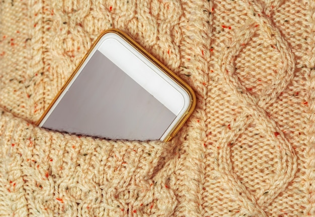 Smartfon z pustym ekranem w kieszeni swetra