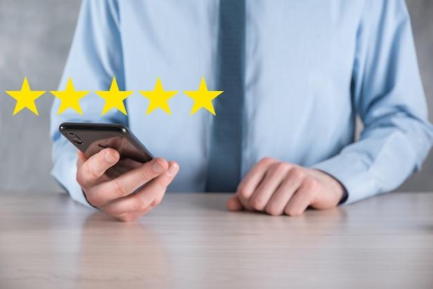 Smartfon z ręką człowieka wyświetlający się na pięciogwiazdkowej doskonałej ocenie. wskazując pięciogwiazdkowy symbol, aby zwiększyć ocenę firmy. przejrzyj, zwiększ ocenę lub ranking, ocenę i koncepcję klasyfikacji