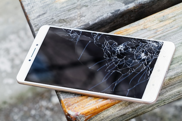 Smartfon z uszkodzonym ekranem leży na drewnianej ławce. selektywne ustawianie ostrości
