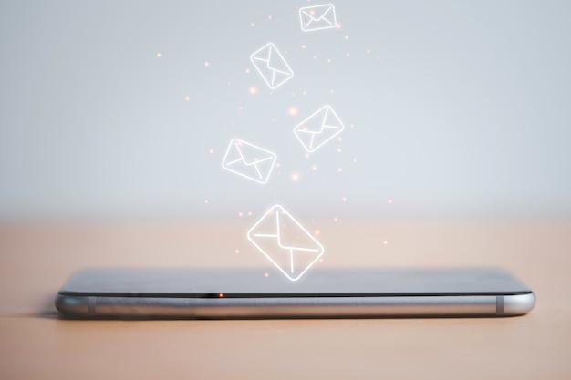Smartfon z wirtualnymi literami do odbierania i wysyłania e-maili