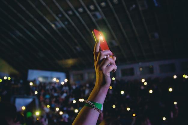 Smartfon z włączoną latarką w kobiecej dłoni na koncercie