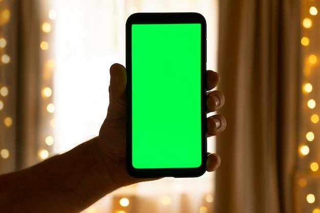 Smartfon z zielonym ekranem makieta ekran z zielonym kluczem chromatycznym telefon jest w dłoni w salonie